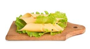 Le fette del formaggio su insalata verde lascia il fondo Fotografie Stock