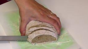 Le fette della donna hanno cotto di recente il pane intero Pane bollente a casa stock footage