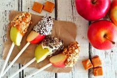 Le fette delle mele hanno immerso con cioccolato, il caramello, scena su legno bianco immagine stock libera da diritti
