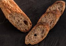 Le fette di baguette alpine casalinghe fresche sono servito sul nero Immagine Stock
