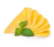 Le fette di formaggio con basilico fresco lascia il primo piano isolato su un fondo bianco Fotografia Stock