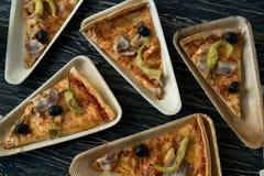Le fette di pizza è su un piatto di legno Immagine Stock