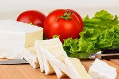 Le fette, i pomodori e la lattuga del formaggio coprono di foglie per la prima colazione su un bordo Fotografia Stock Libera da Diritti