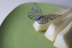 Le fette succose di melone si trovano su un piatto verde Su loro è una decorazione, un taglio della farfalla da una stagnola Immagini Stock