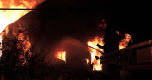 Le feu énorme flambant en feu de maison et le sapeur-pompier pulvérisent l'eau avec le tuyau dans l'ombre banque de vidéos