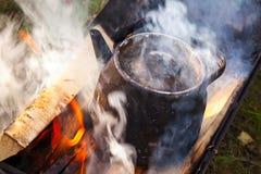 Le feu avec de la fumée, metal la vieille théière de ébullition noire photographie stock