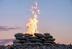 Le feu brûlant dans l'endroit en pierre sur la plage de galets Photo stock