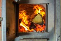 Le feu brûle dans le fourneau, bois de bouleau, sauna image stock