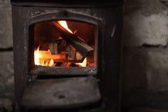 Le feu brûlant dans le petit fourneau noir de fer photos stock