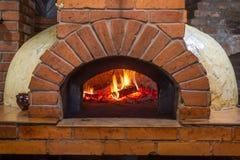Le feu brûle dans un four en bois de pizza Photos libres de droits