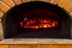 Le feu brûle dans un four en bois de pizza Photographie stock