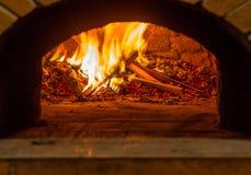 Le feu brûle dans un four en bois de pizza Photos stock