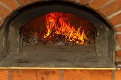 Le feu brûle dans un four en bois de pizza Images stock