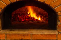 Le feu brûle dans un four en bois de pizza Photo libre de droits