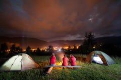 Le feu d'observation de personnes ensemble près du camp et des tentes dans l'obscurité Photographie stock libre de droits