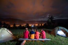 Le feu d'observation de touristes ensemble près du camp et des tentes dans l'obscurité Image libre de droits