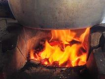 Le feu dans le fourneau chauffe le pot sur le dessus photos libres de droits