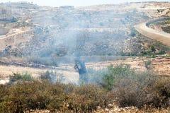 Le feu dans un domaine palestinien par le mur de la séparation Photographie stock