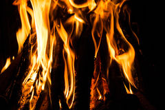 Le feu dans un feu de cheminée flambe sur un fond noir Images stock