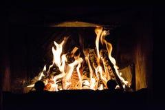 Le feu dans un feu de cheminée flambe sur un fond noir Image stock
