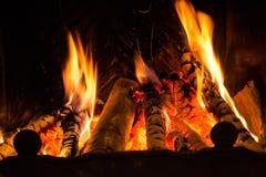 Le feu dans un feu de cheminée flambe sur un fond noir Image libre de droits