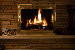 Le feu dans une cheminée avec le mantel en pierre Photos libres de droits