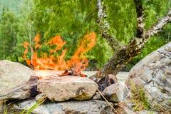 Le feu de camp Feu dilué dans les roches dans la perspective de la forêt photo stock