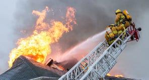 Le feu de flambage de maison de bataille de sapeurs-pompiers images libres de droits