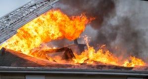 Le feu de flambage de maison de bataille de sapeurs-pompiers images stock