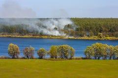 Le feu de forêt sur la rivière de Desna de banque avec les prés en crue et les beaux champs Images libres de droits