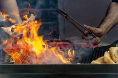 Le feu de gril de barbecue avec des mains Photographie stock