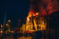 Le feu de nuit dans l'immeuble, sapeurs-pompiers luttent avec la flamme, les gens se tiennent autour Catastrophe du feu et tragéd photos stock