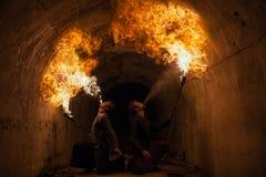 Le feu de soufflement de jeune homme de sa bouche Photographie stock libre de droits