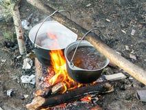 Le feu de touristes avec faire cuire des pots avec l'eau bouillante image libre de droits