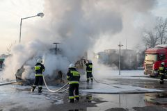 Le feu de voiture à la station service Fourgon et sapeurs-pompiers brûlants s'éteignant un feu image stock