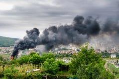 Le feu et fumée au-dessus de la ville Photo stock