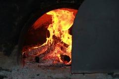 Le feu lumineux brûlant dans le four couvert de rail de porte Images stock