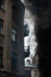 Le feu pendant des émeutes urbaines, beaucoup de fumée Protestataire observant du balcon du feu Image libre de droits
