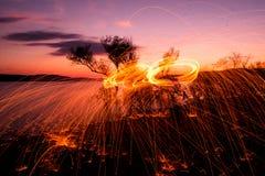 Le feu POI au coucher du soleil sur le lac Photo libre de droits