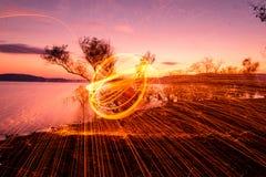 Le feu POI au coucher du soleil sur le lac Images libres de droits