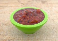 Le feu rôti a écrasé des tomates dans une cuvette verte Photo stock