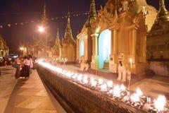 Le feu s'est allumé pour la prière chez Crowded et la pagoda de Shwedagon le soir pendant le coucher du soleil Photos libres de droits