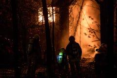 Le feu spectaculaire de maison, pompiers utilisent le tuyau dans l'ombre image libre de droits