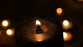 Le fiamme da una candela a prova di fuoco del grande ferro nello scuro e giro dell'ustione del fondo sul piccolo video d archivio