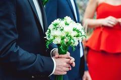 Le fiancé dans un costume bleu-foncé juge un bouquet de mariage fait de fleurs blanches Images stock