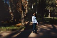 Le fiancé marche autour du parc dans les lumières du coucher du soleil Images libres de droits