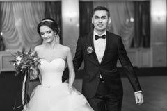 Le fiancé sourit à l'appareil-photo tout en menant la jeune mariée au premier Dan Photos stock