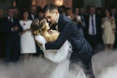 Le fiancé tient la jeune mariée dans des ses mains tout en dansant dans la fumée Photo libre de droits