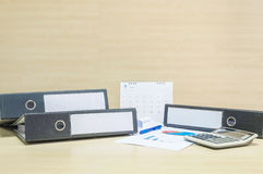 Le fichier document de plan rapproché et le papier et la calculatrice de travail dans le concept de dur labeur sur le bureau et l Photographie stock libre de droits