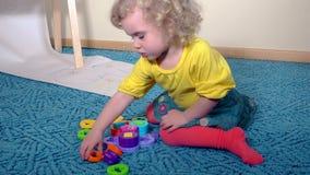 Le fiddle di plastica stabilite del giocattolo del bambino astuto sveglio della ragazza collegano la seduta sul pavimento di tapp video d archivio